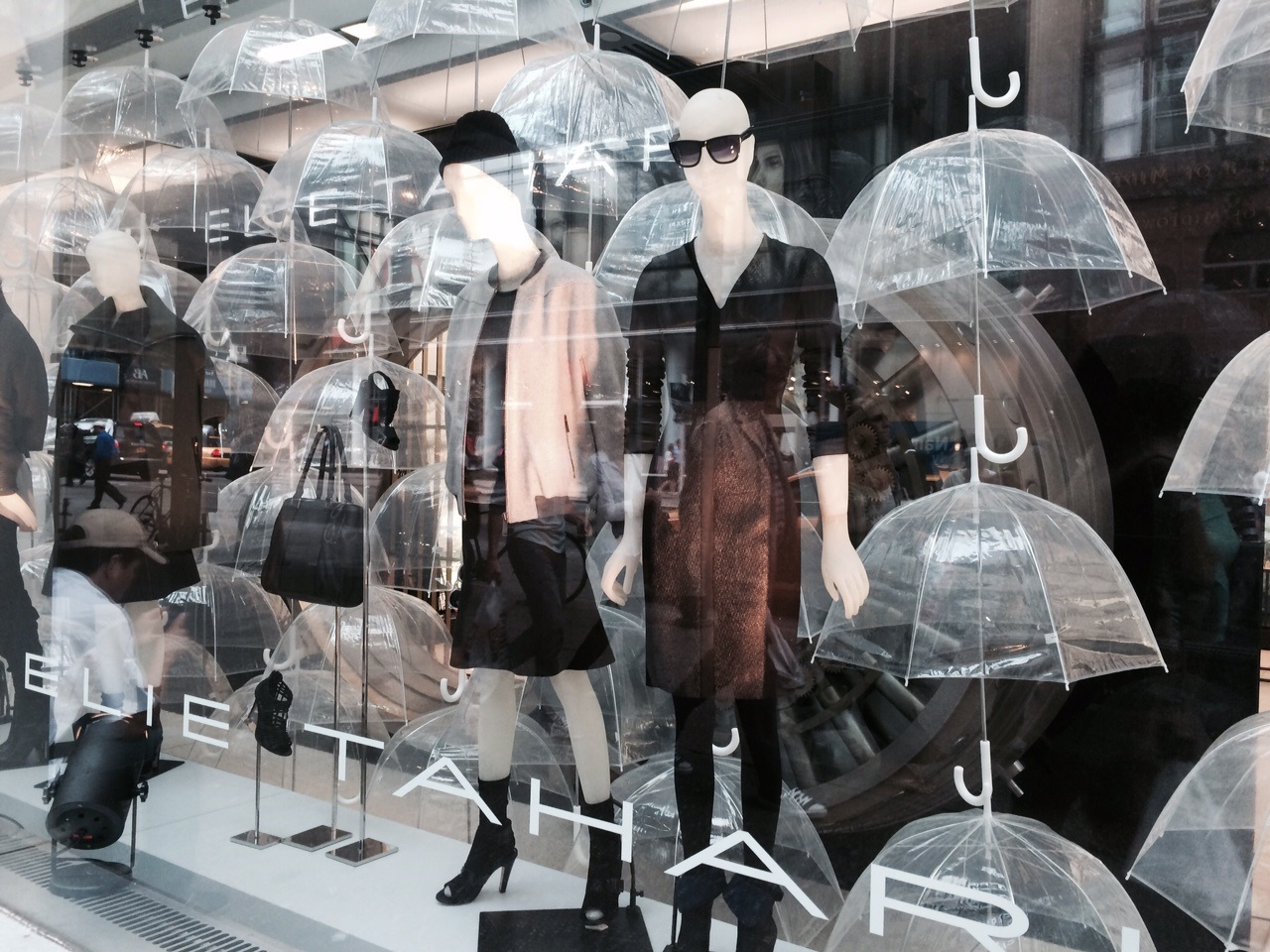 This window display is marking the autumn with lots of hanging umbrellas and dark autumnal colors on clothes.