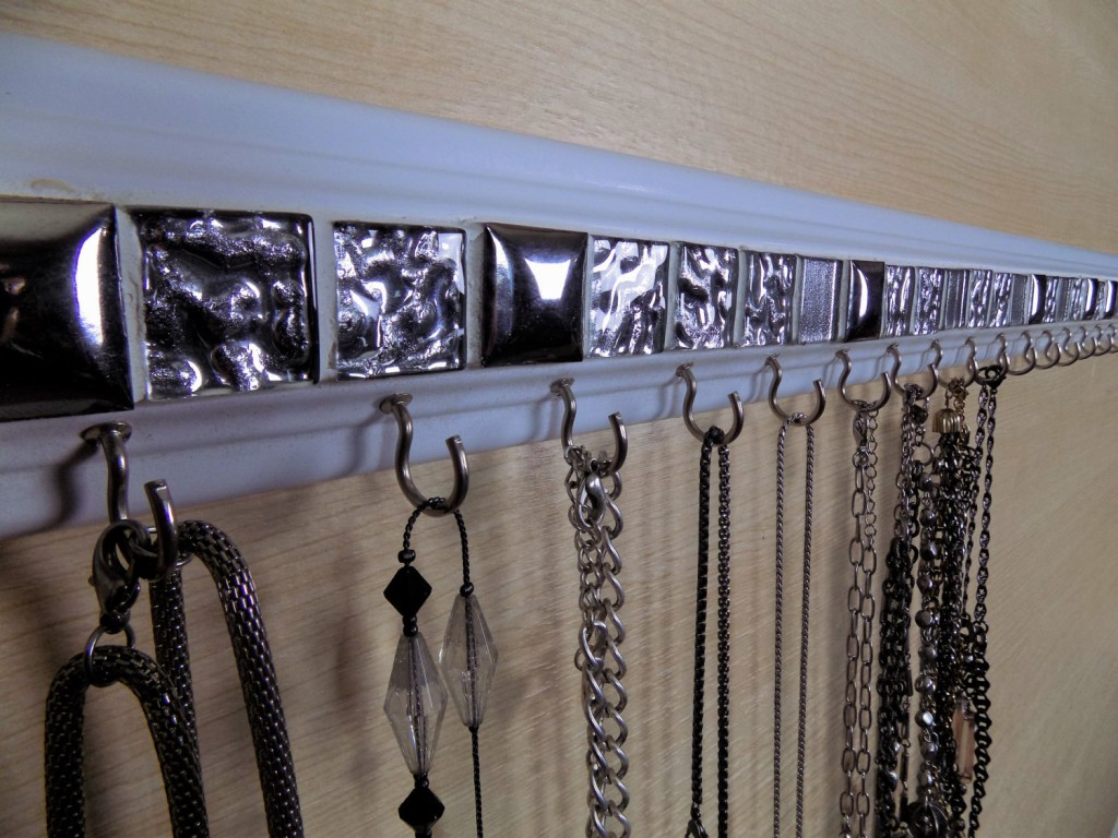 A creative jewelry necklace holder, attractive and functional made of wood, metal and glass mosaic tiles.