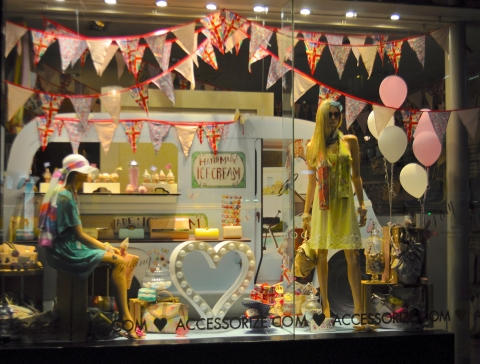 In this window display mannequins are looking sophisticated but that van in the back and the handmade ice cream makes you think about a hippie summer.