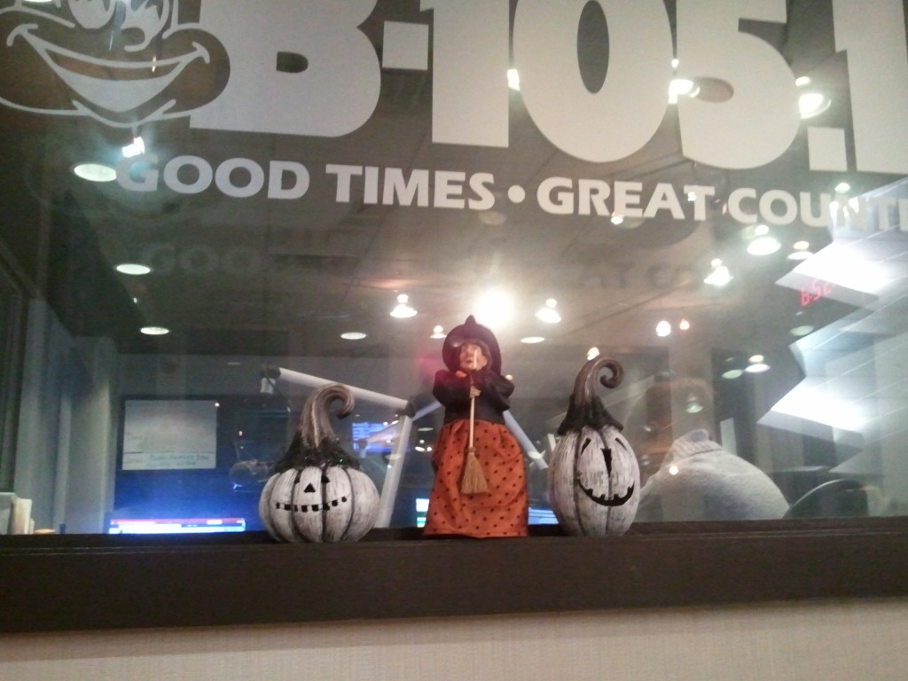 In this Halloween window display we have two white, smiling pumpkins and an old witch standing between them.