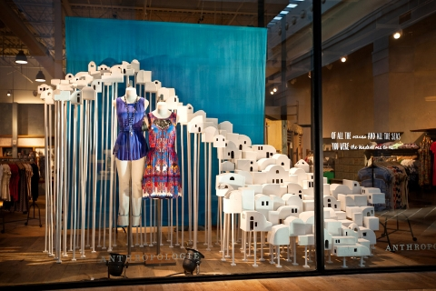 Little white houses and a blue background to create the idea of summer in this Anthropologie window display.