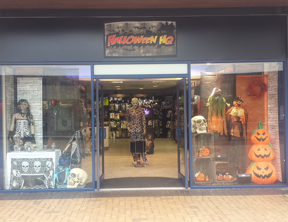 Zombies in the window display, pumpkins, lots of skulls and also a standing zombie in the front door of the store, it's definitely Halloween.