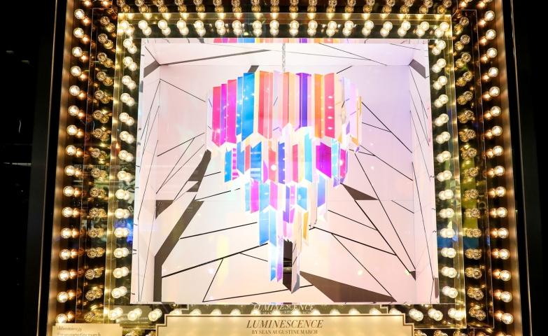 An abstract way to create a Christmas window display, with many lights bulbs, and in the middle some geometric shapes with colors with the theme of Luminescence.