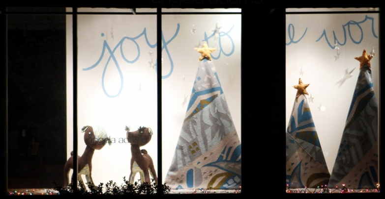 """Angela Adams gallery has plush dogs, tents with a star on the top and a """"Joy to the world"""" message for the New Year's Eve window display."""