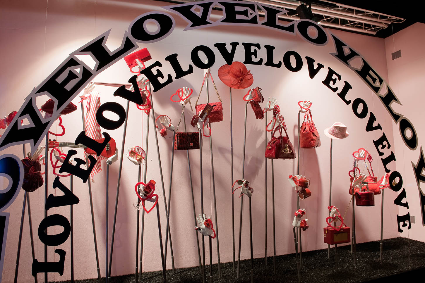 The window display is designed with an arch of love stickers, and red purses, to be in theme with Valentine's day.