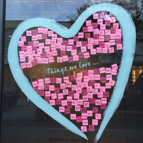 The Banana Republic has a blue heart filled with sticky notes about things we love, as a design for the Valentines' day window display.