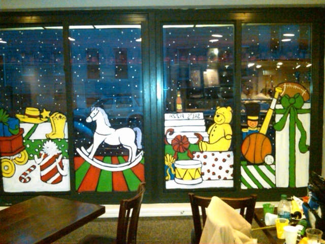 This Brooklyn pizza restaurant was wishing happy New Year's Eve by painting some cool holiday stuff on the window display.