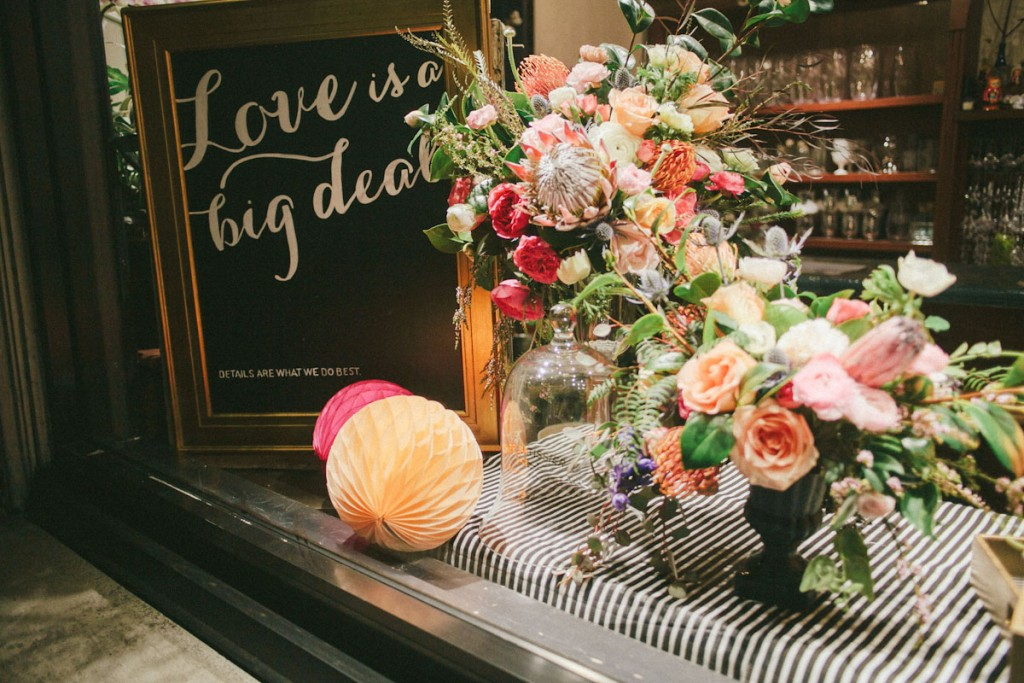 This chic window display is made for Valentine's day with flowers and a blackboard with a golden frame sending a message about love.
