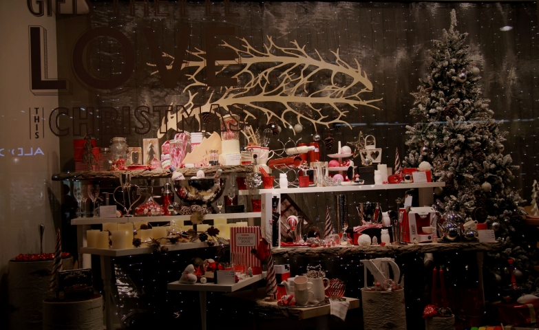 You cannot be bored with candles and so many red objects, a snowed fir and Christmas lights all in this window display.