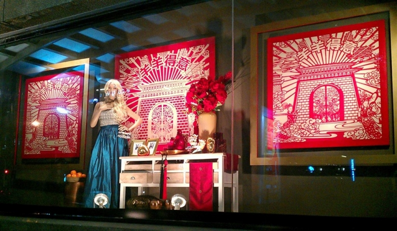 Another representation of New Year's Eve window display, through beautiful Chinese elements, red flowers, red and white pictures in the background, and gorgeous dress on the mannequin.