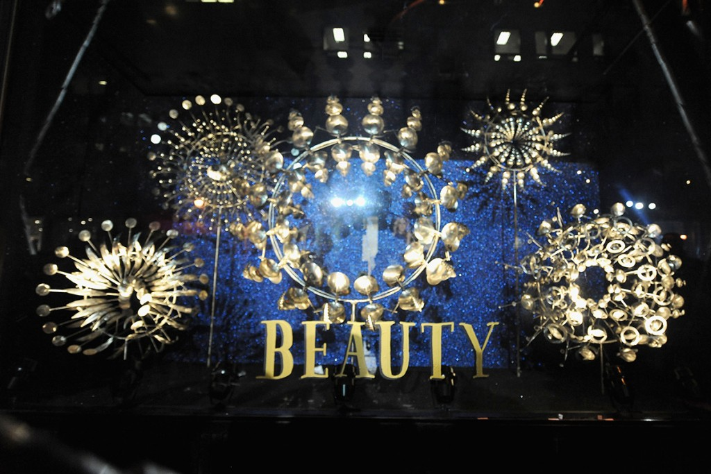 Beauty theme for New Year's Eve window display, with golden circles accompanied by elements which look like petals and make the circles looking like flowers, and the blue background looks like a night sky.