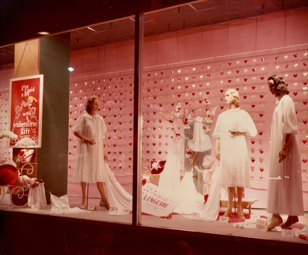 A classic example of a vintage Valentine's day window display with white clothes, pink light and red little hearts in the background.