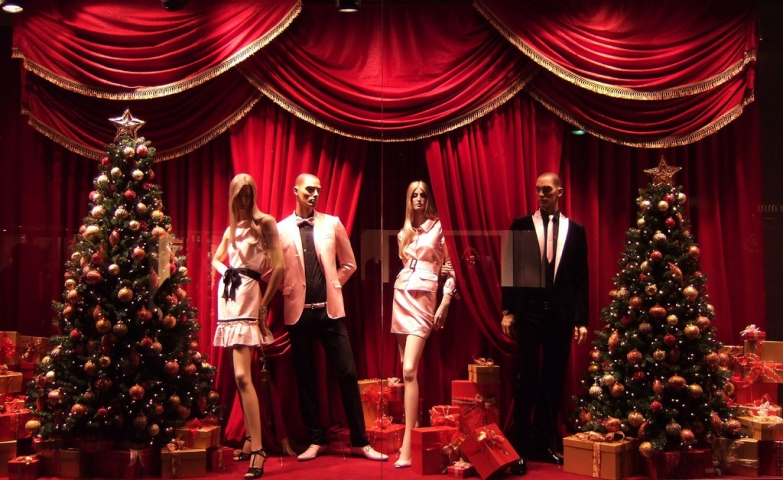 At Dolce & Gabanna, Christmas is celebrated in a classic way through the window display, with two couples of mannequins, two adorned firs, and a big red curtain.