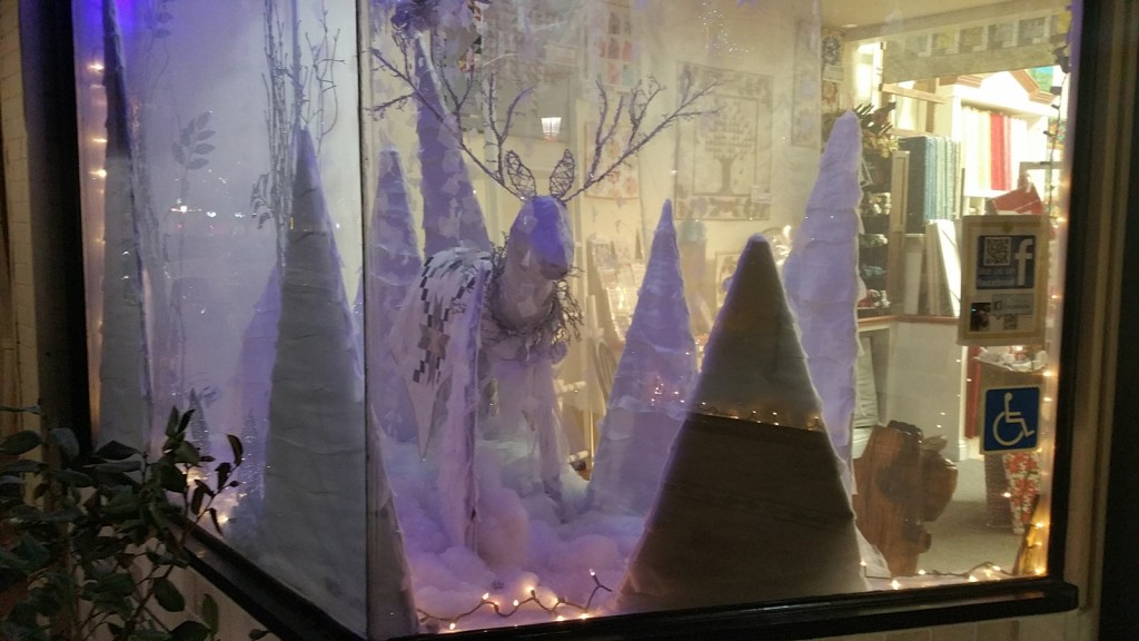 The white decor, the patterns blanket covering the deer, and the floes around, give this New Year's Eve window display a coolness.