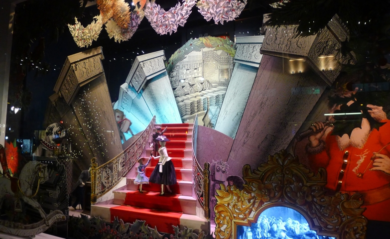 A royal Christmas window display with a castle layout, and two dolls climbing the stairs.