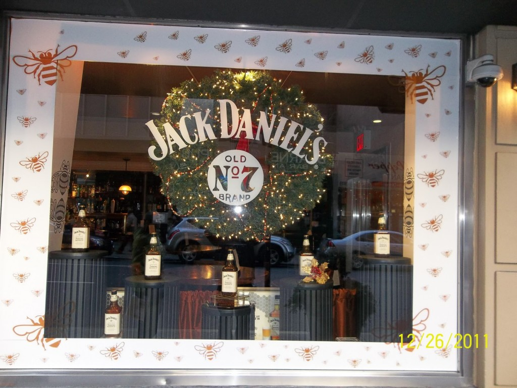 "The wreath placed in the back of the window display made a good contrast between the white written ""Jack Daniel's"", and the lights are just on point for New Year's Eve. The frame with bees from outside the window is giving a friendly air."