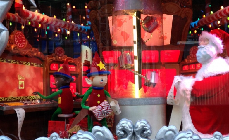 On a red decor, in this window display, Santa is talking with his best elf about the Christmas list of gifts.