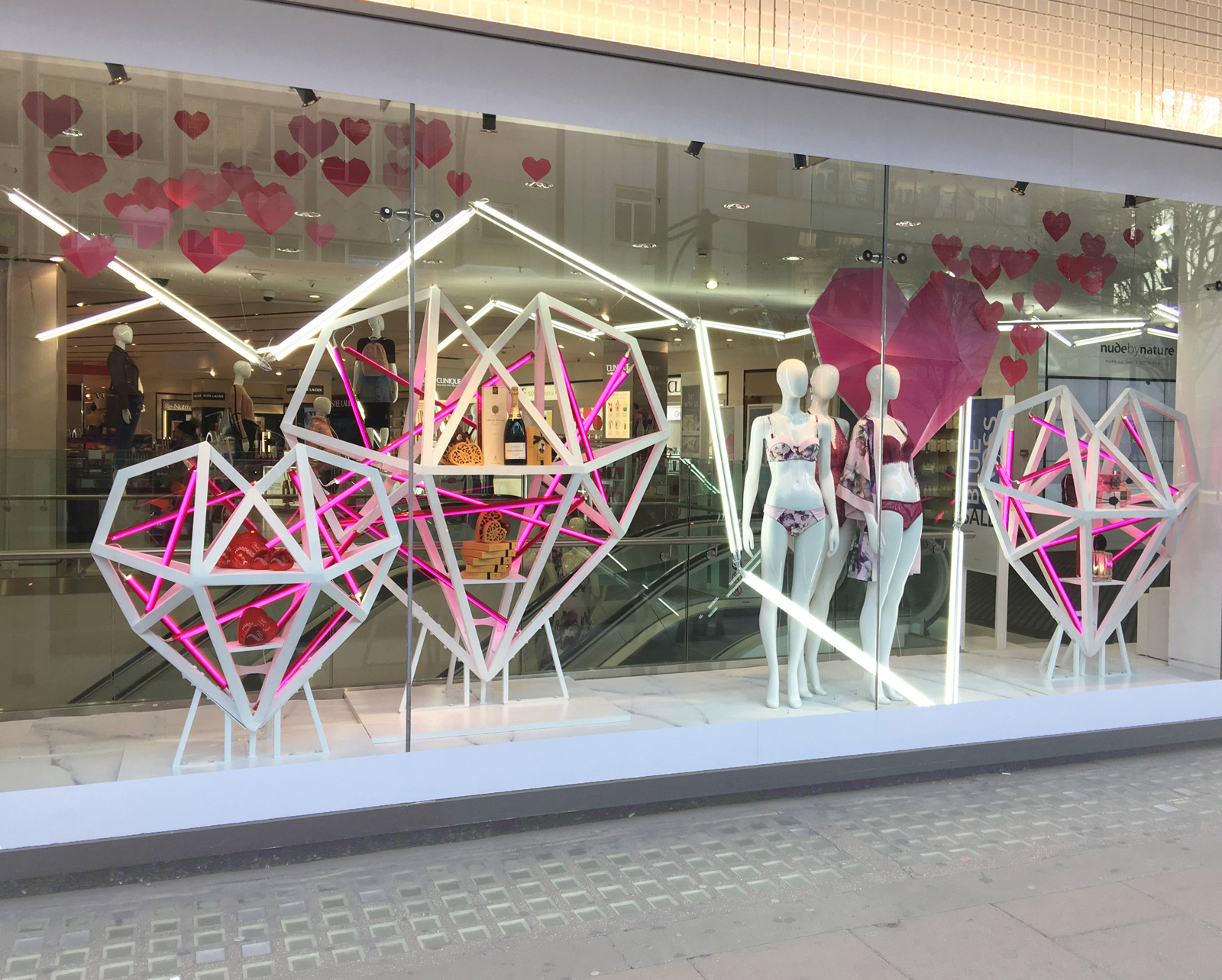 Debenhams Valentine's day window display is about a wooden pink & white heart and mannequins with underwear.