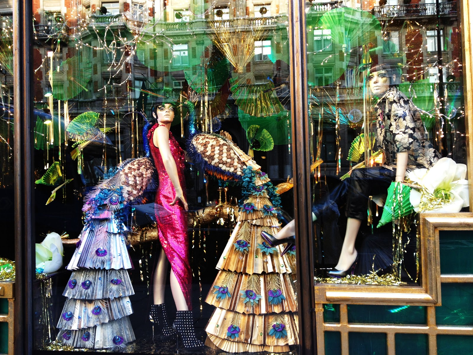 A glam way to design the New Year's window display, with two peacocks in beautiful colors and mannequins dressed festively.