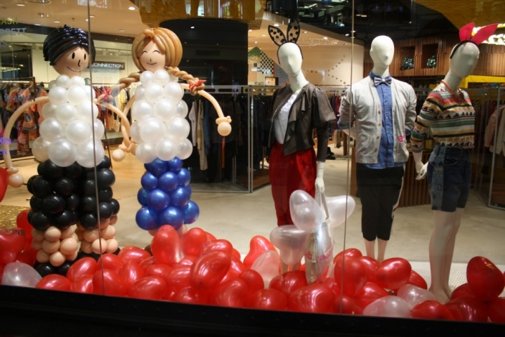 DiffereDifferent balloons colors, happy puppets, and mannequins with bunny ears for this Valentine's Day window display.nt balloons colors, happy puppets, and mannequins with bunny'ears for this Valentine's Day window display.