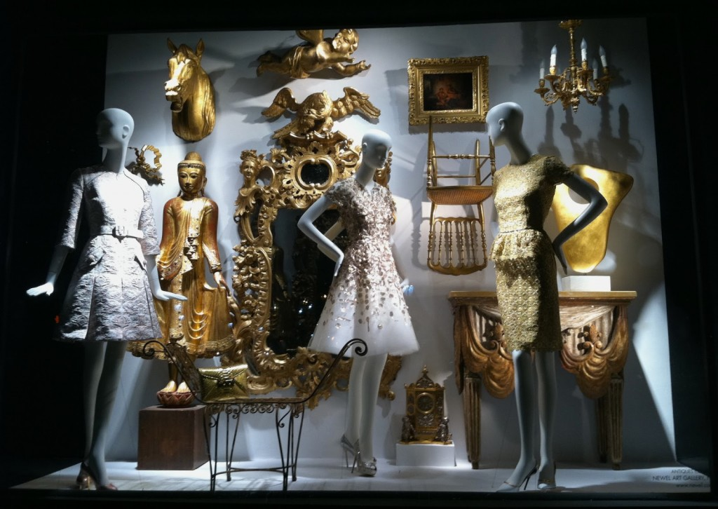 An elegant New Year's Eve window display, with a golden chair, a mirror, a picture frame and other sculptures, also beautiful dresses on the mannequins.