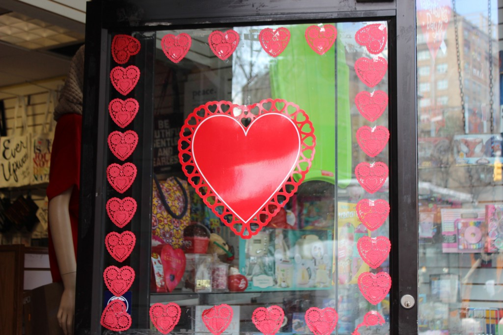 The window display's door, has little hearts stickers on sides and another big & red heart in the middle, for the big lovers of the Valentines'Day.