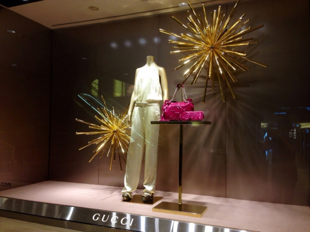 Gucci store has made a brilliant New Year's Eve window display, by putting in the back of the white costume and the pink handbag, golden fire-crackers, made from a sort of foil fabric.