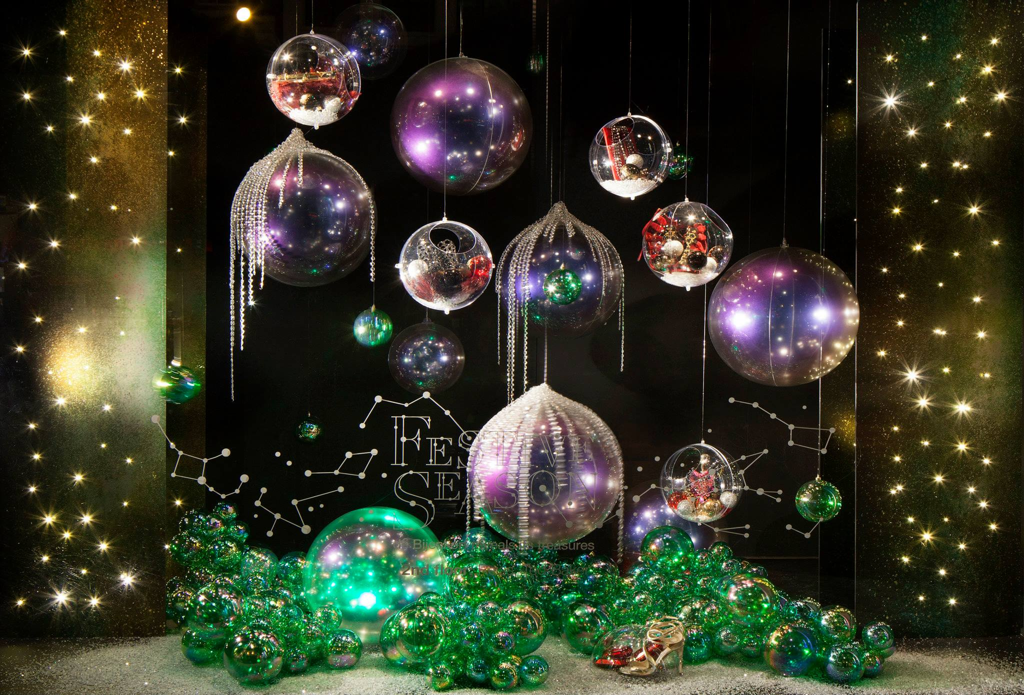 All together in this window display, big and small spheres colored in green and purple, designed for Christmas, the most festive time of the year.