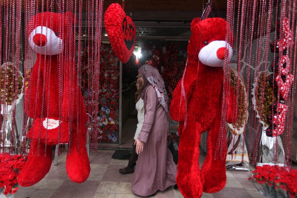 Giant plush toys in front of a window display, ready to celebrate Valentine's Day.