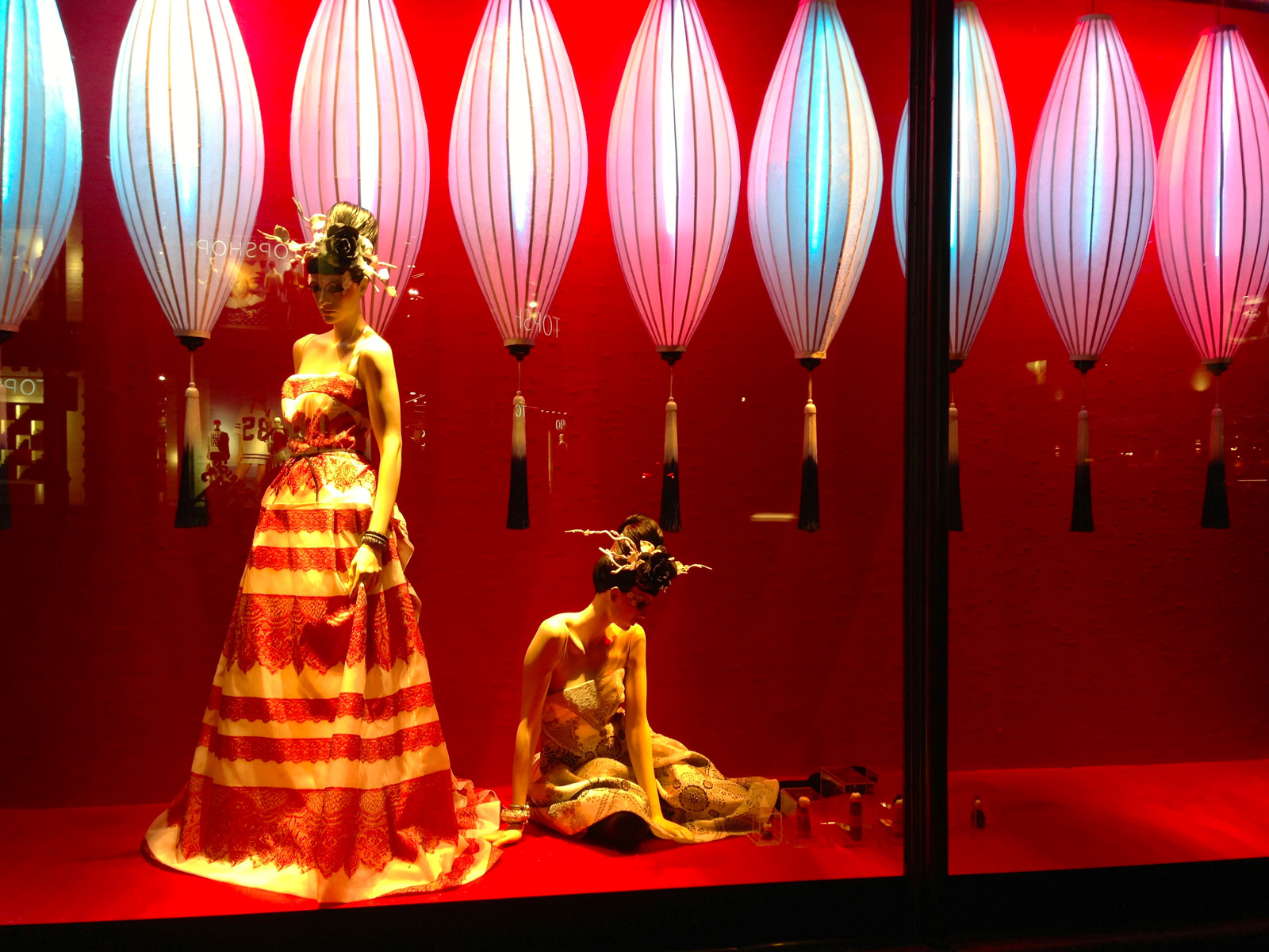 The clothes and the colored lanterns from this window display are indicating that it's about the Chinese New Year's Eve.