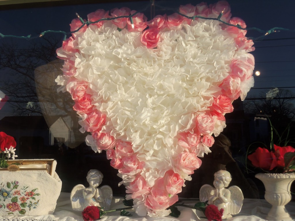 The pink & white heart, made from fabric roses, placed in this window display, is very prominent, but you should also observe the cupids from the sides of the heart, which are beautiful for Valentine's day decoration.