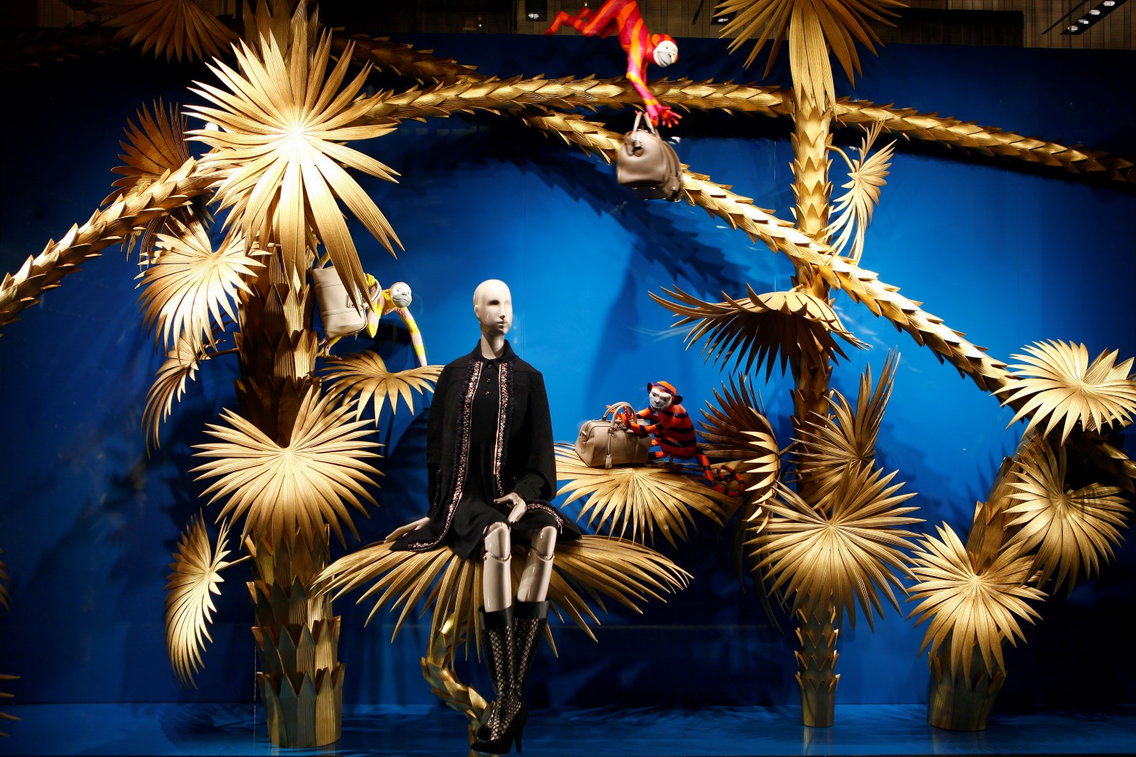 The blue background and the idea of palm trees could be for a summer window display but the golden leaves that are looking like fire-crackers, and the vestment of the mannequin could indicate a New Year's Eve time for Louis Vuitton.