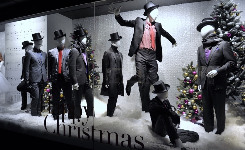 Holt Renfrew is wishing happy Christmas through the design of the window display, with mannequins dressed in black costumes, being in contrast with the white background.
