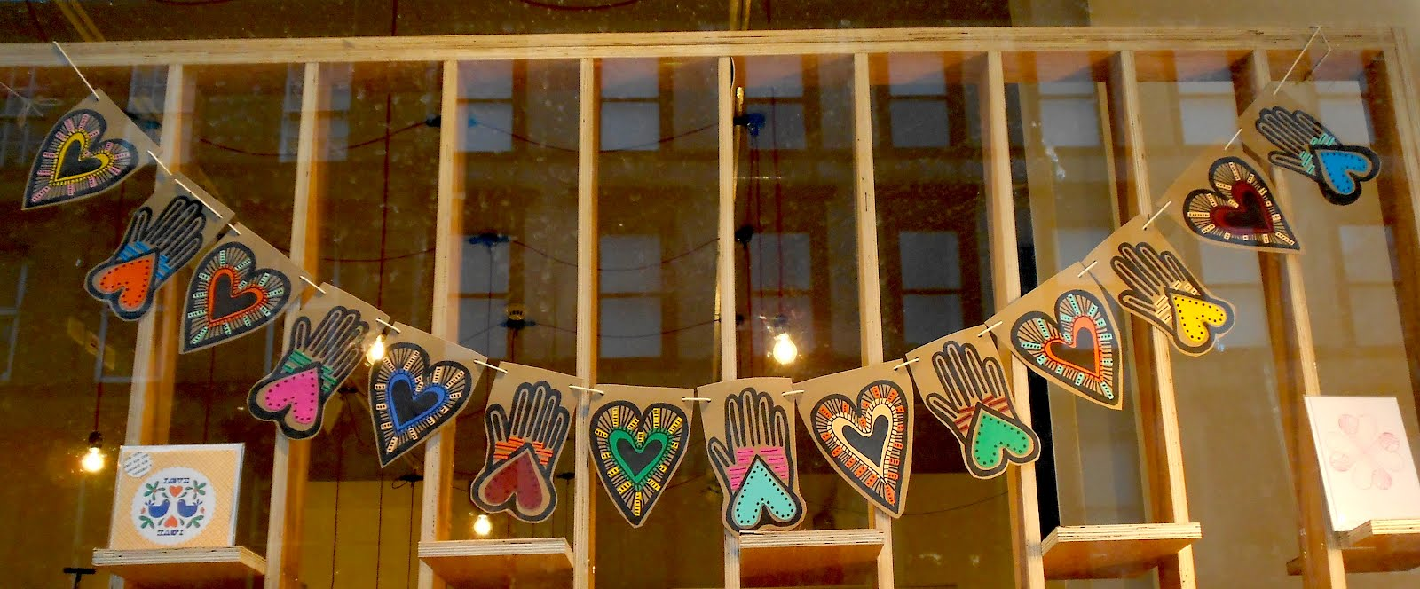 Cute window display decorated for Valentine's day with hanging hearts and hands illustrations.