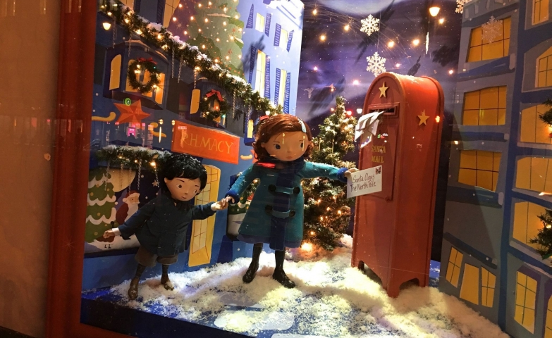 A Christmas window display with a scene in which two kids are sending a letter to Santa.