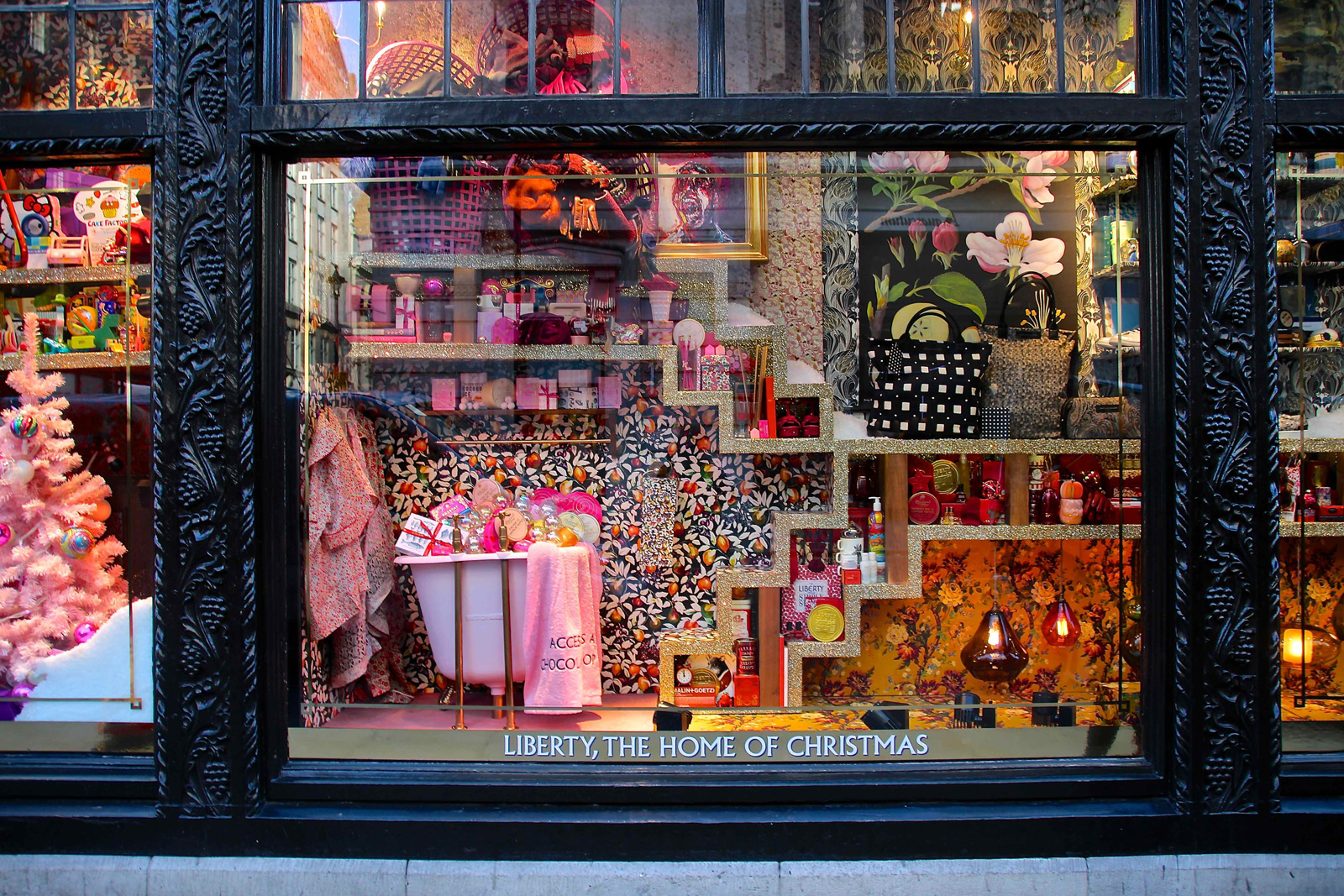 At liberty home of Christmas, the window display is full of patterns, prints most in pink but also in orange and black.