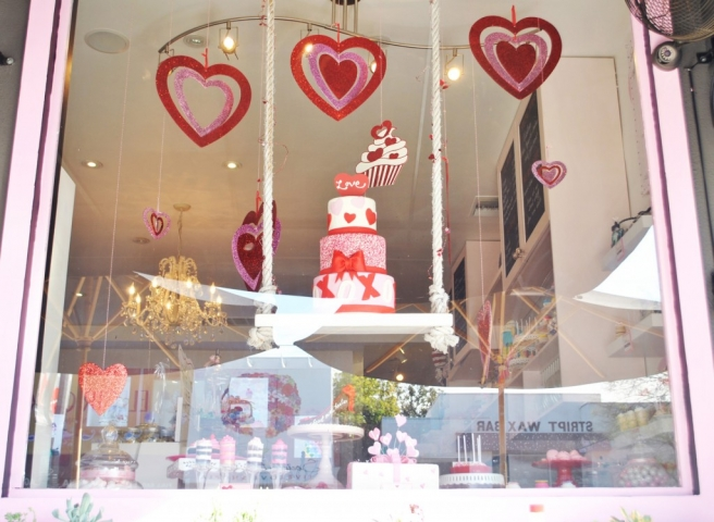 This Valentine's Day window display is decorated with red and pink hearts and also a big 3 tier cake with a heart on the top.