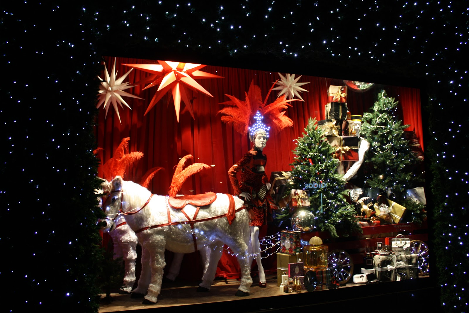 The main theme of this Christmas window display is two little horses with a charged carriage with adorned firs and presents.