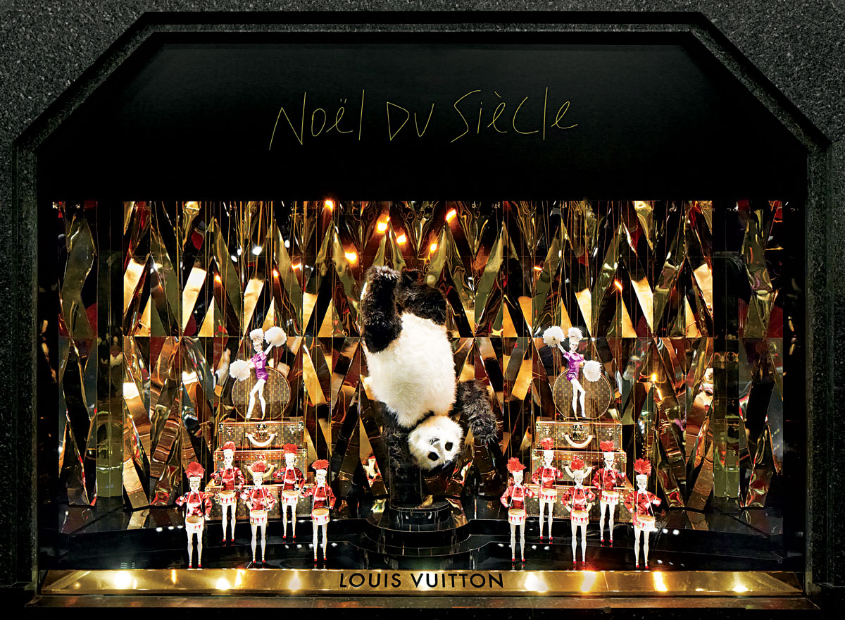 "Louis Vuitton has a theme called ""Noel du Siecle"" which is represented by gold mirrors, and puppets having a show in the Christmas window display."