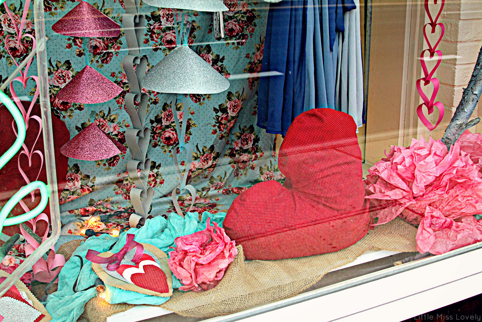 A lovely & cozy Valentine's Day window display decoration with a big, red pillow in the shape of a heart, another little hearts of paper and a curtain with flowers.