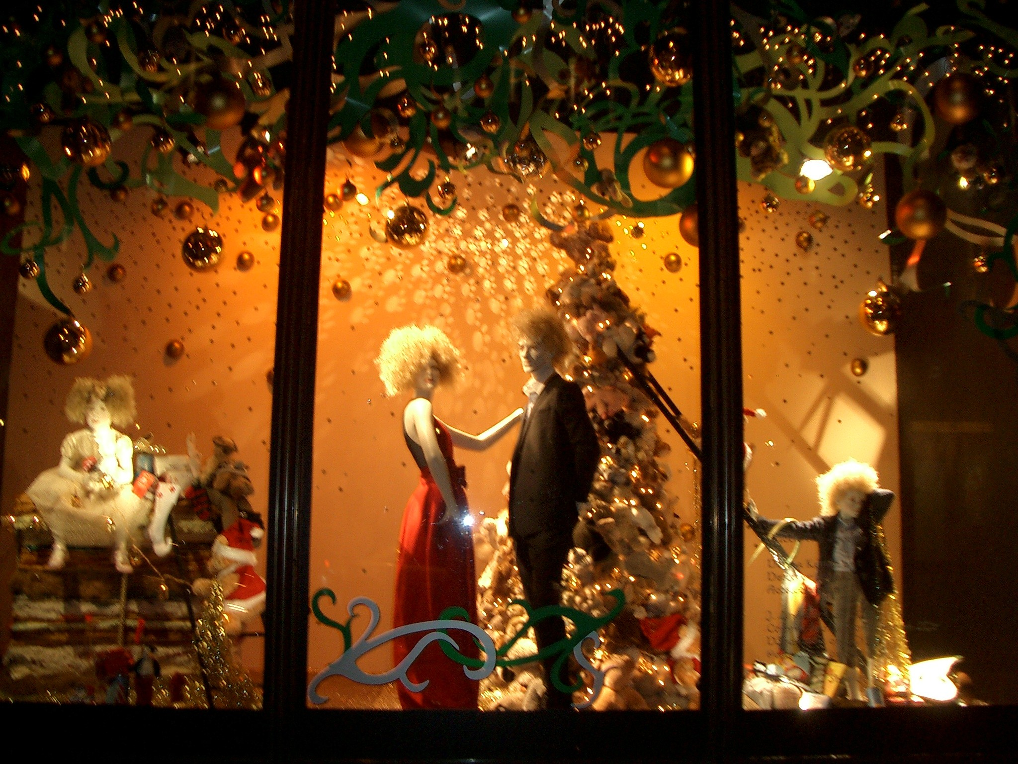 A magic Christmas night near the white fir and under the green tinsels, for two elegant dressed mannequins from this window display.