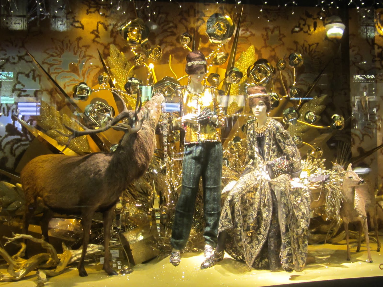 In this Christmas window display, we can see two mannequins near a deer, and many golden details, in theme with the holidays.