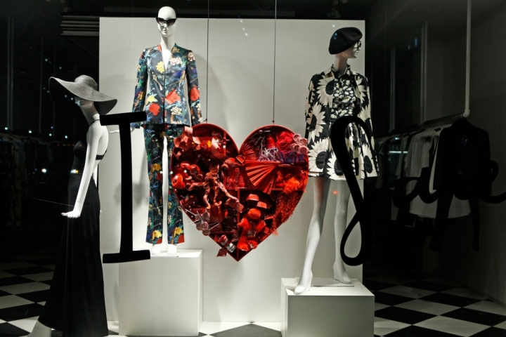 Mostly black & white, this window display, has only one hanging heart filled with abstract elements, between two mannequins, for Valentines' day.