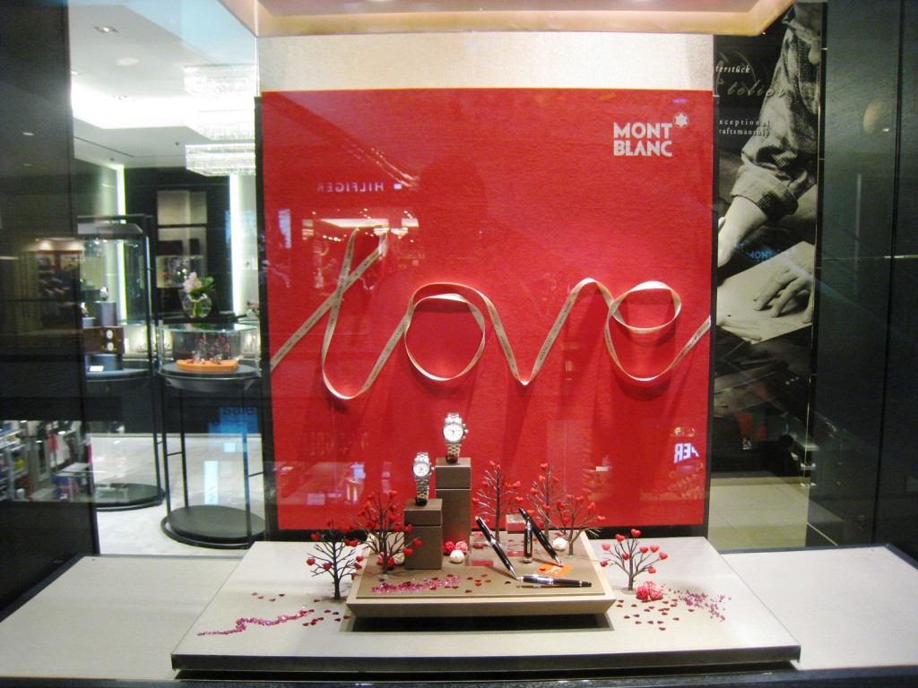 "Mont Blac made a window display based on red and hearts: The background is red and a garland forms the word ""love"". In front of this background there is a tiny salver that has little trees with hearts instead of leaves."