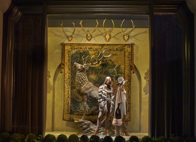 Ralph Lauren has a New Year's Eve window display with a deer on the background, two mannequins, and curtains on the sides.