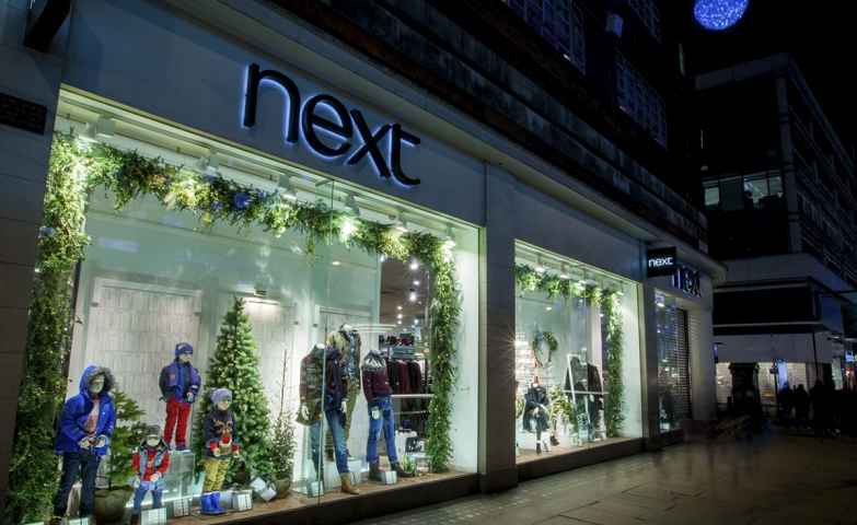 At Next, the Christmas window display is simply decorated with an adorned fir with lights and a decorated window with fir branches.