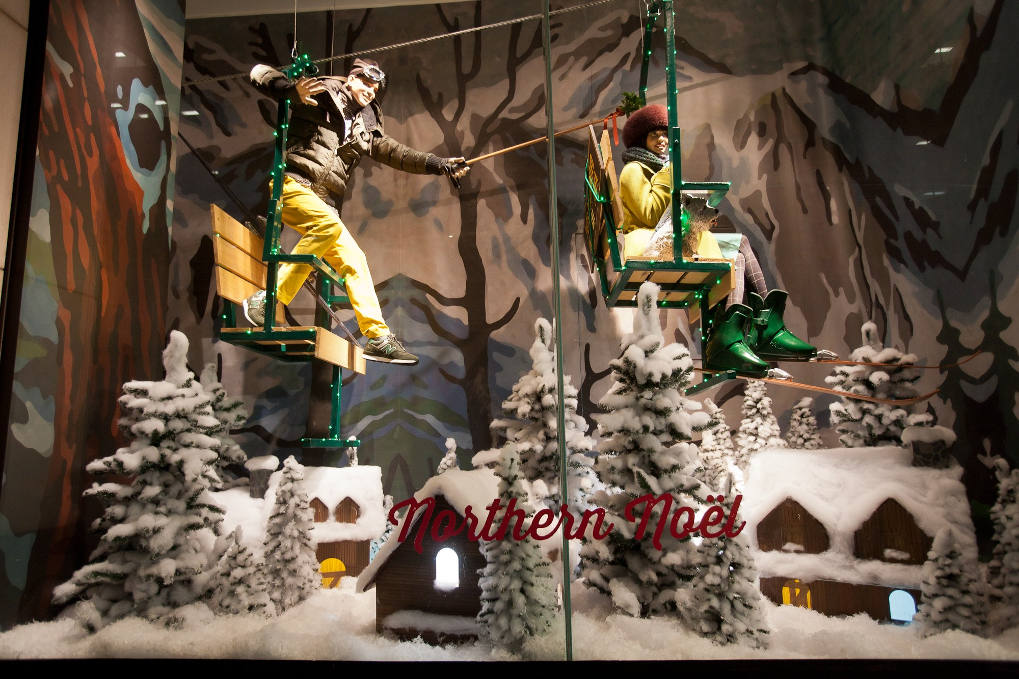 In this Nothern Noel decoration for the Christmas display, we have two playful mannequins in chairlifts, snowed firs and a forest canvas.