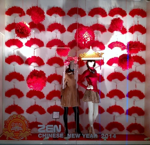 Something apart with those red fans in the background, and the Chinese roof instead of a hat, a Zen New Year's Eve window display.