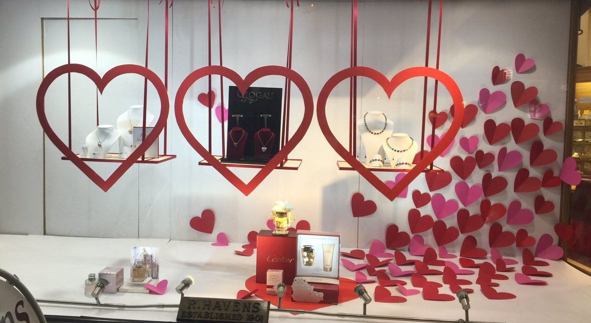 Paper hearts on the right side and frames in shape of hearts that are focusing jewelry for Valentine's day in the window display.