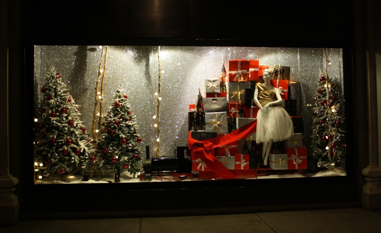 Let's get into the Christmas spirit with this beautifully wrapped presents and firs adorned with red spheres, like in this window display.